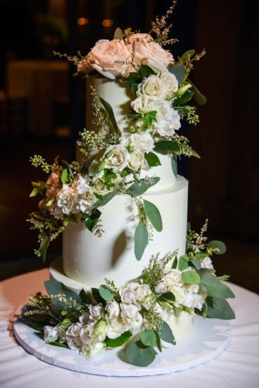 White wedding cake covered in roses and greenery