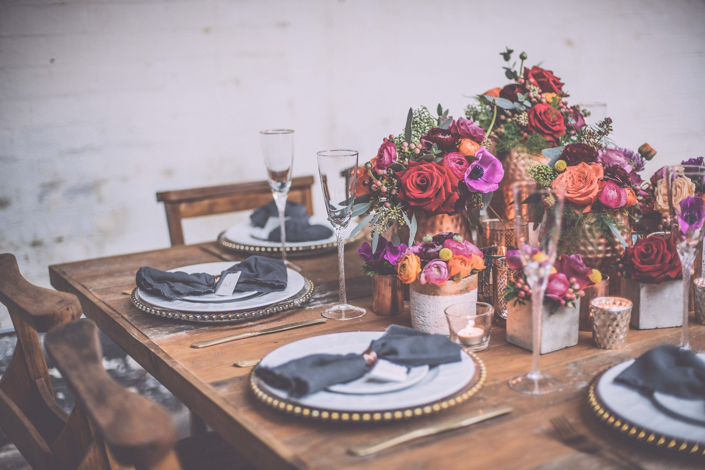 farmhouse table with gold beaded charger and bright flowers