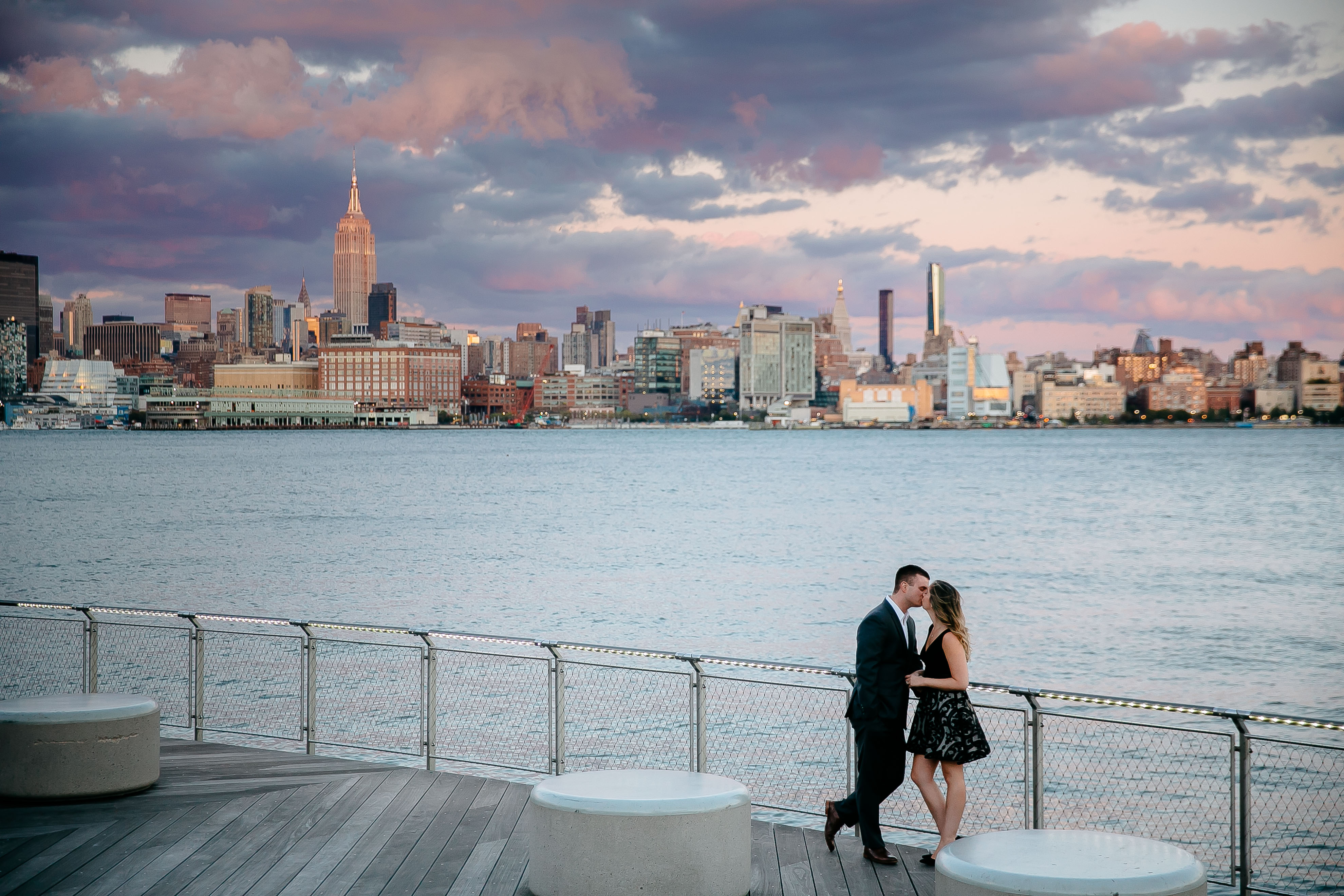 couple kissing by water and NYC skyline