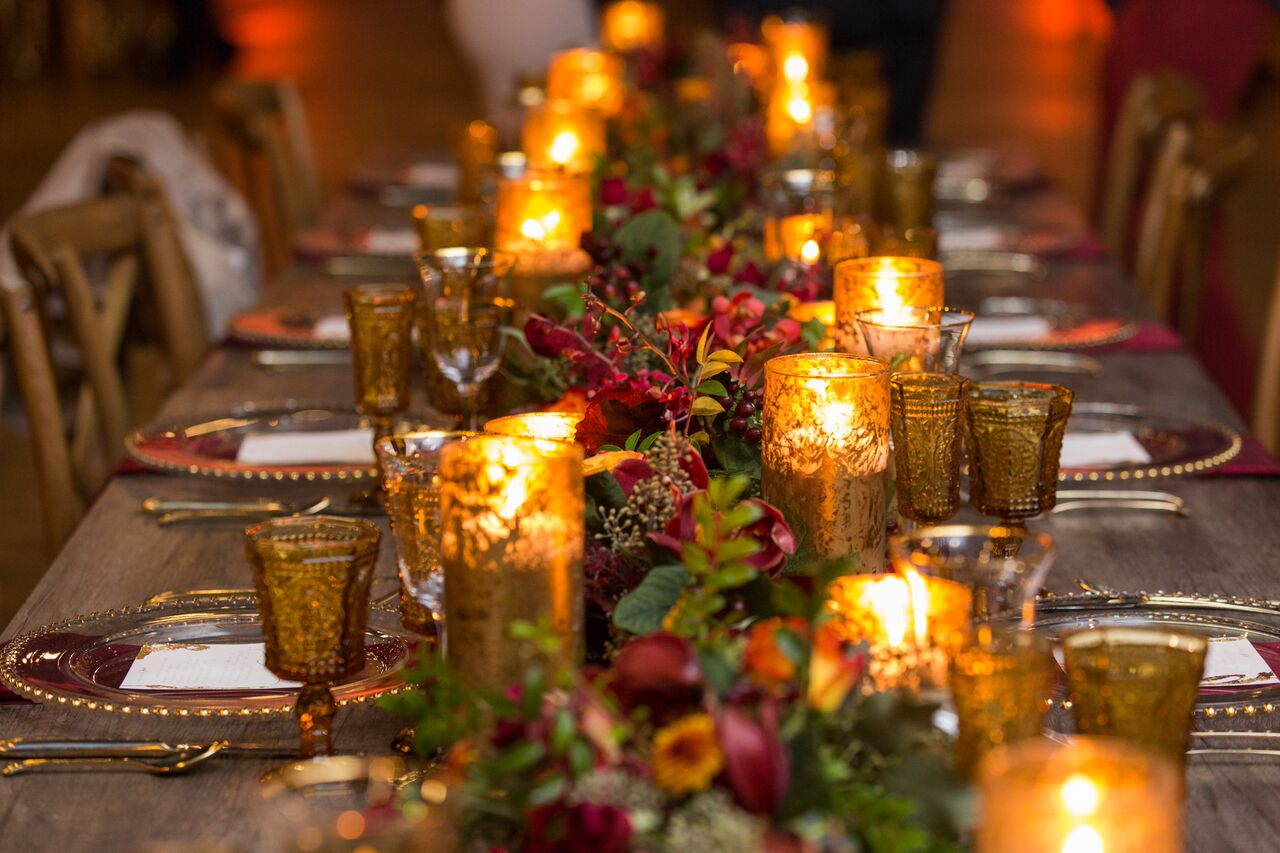 long farmhouse table with green garland and red flowers with gold candles down middle