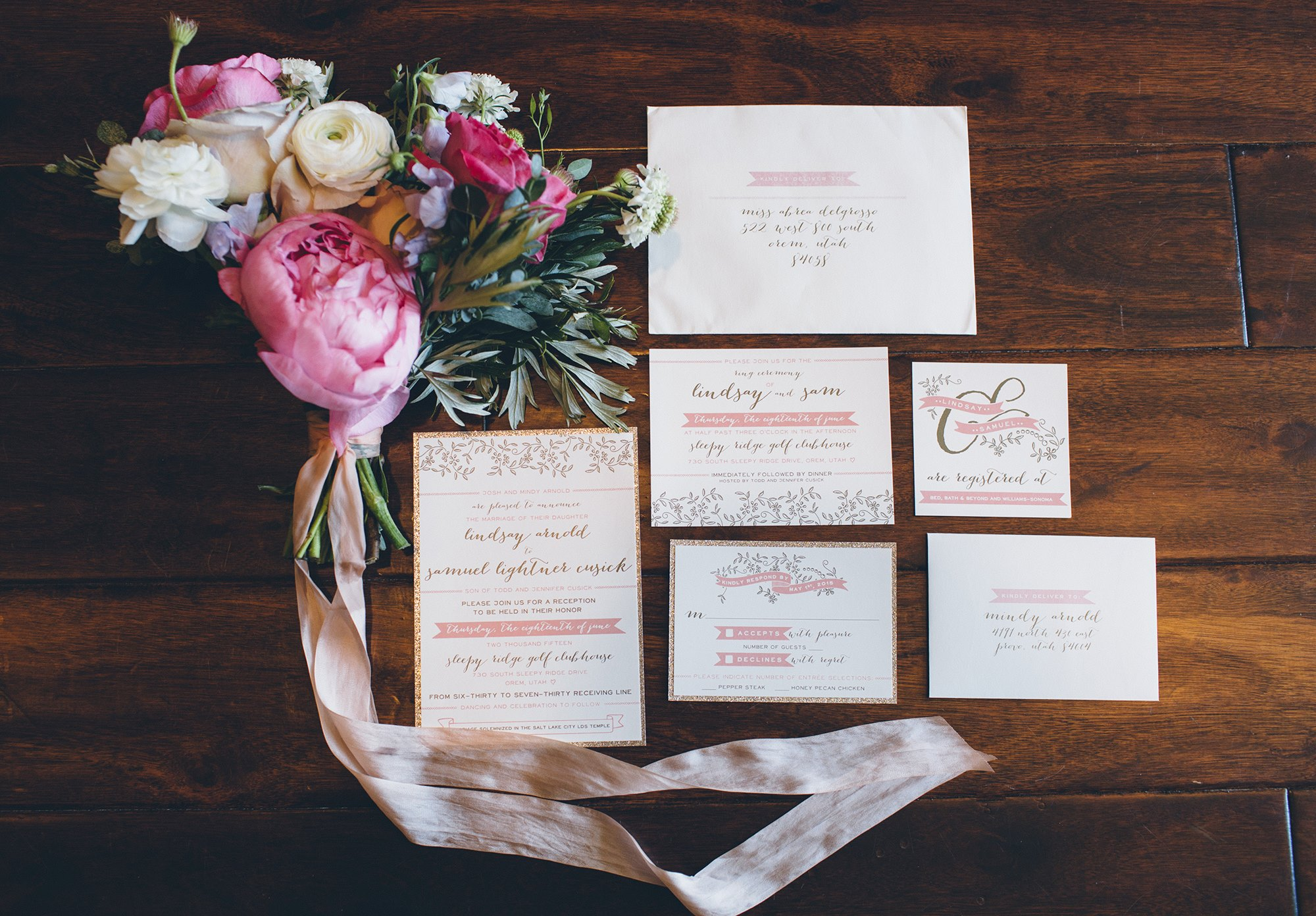 pink and white wedding invitation suite with pink, white and green bridal bouquet