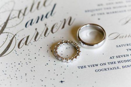 silver and diamond wedding bands on top of sparkly wedding invitation