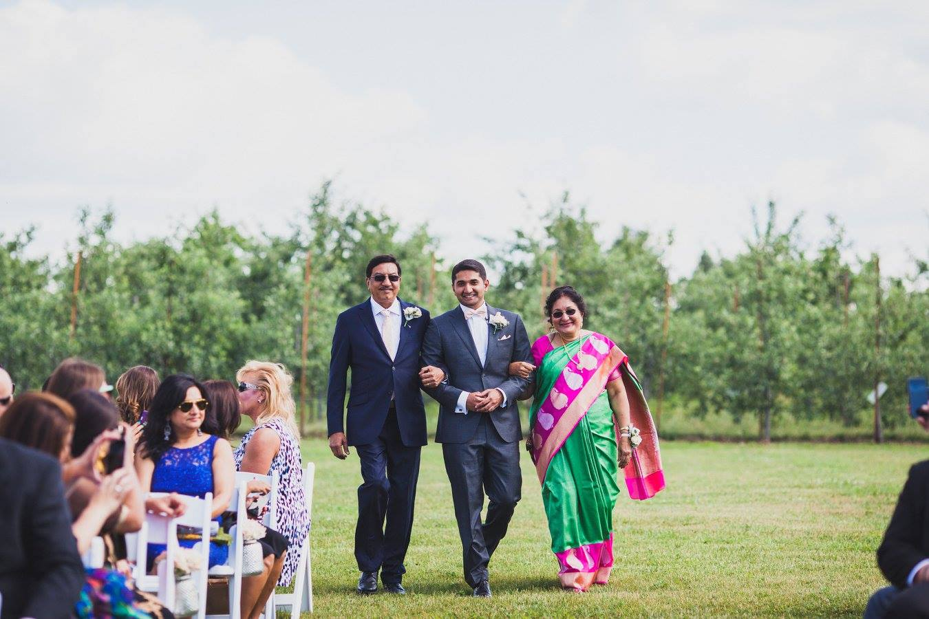 groom walking down the wedding aisle with both parents outside