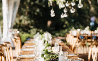long farmhouse table with greenery hanging above for a wedding