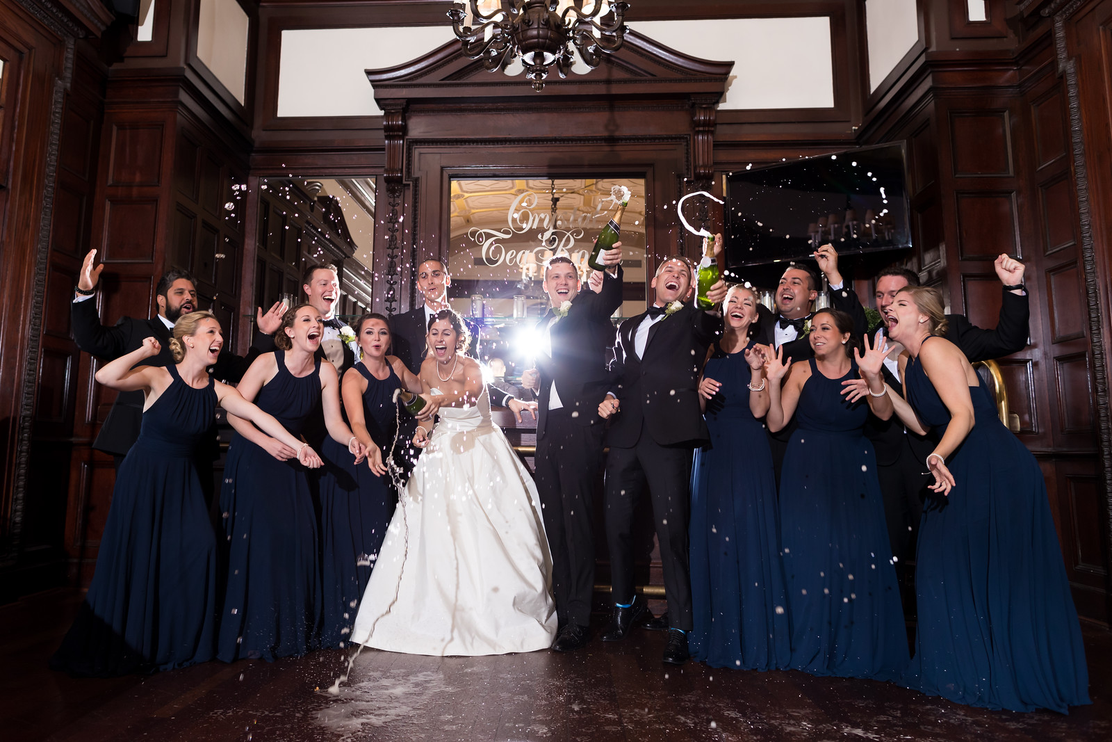 bride groom and party popping champagne