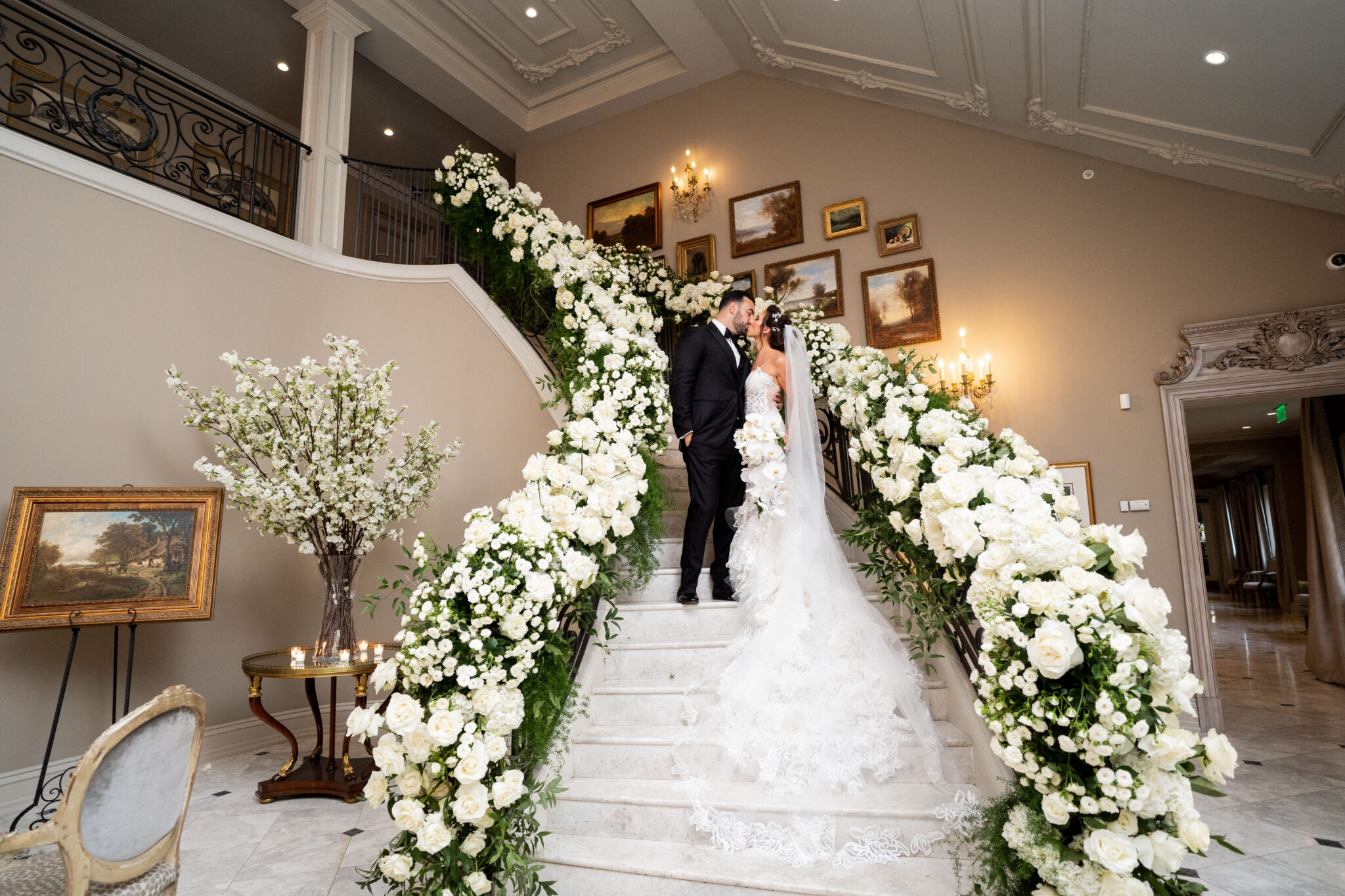 white and green floral staircase with bride and groom