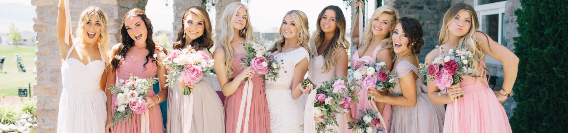 bridesmaids wearing shades of pink lifting bouquets with bride outside