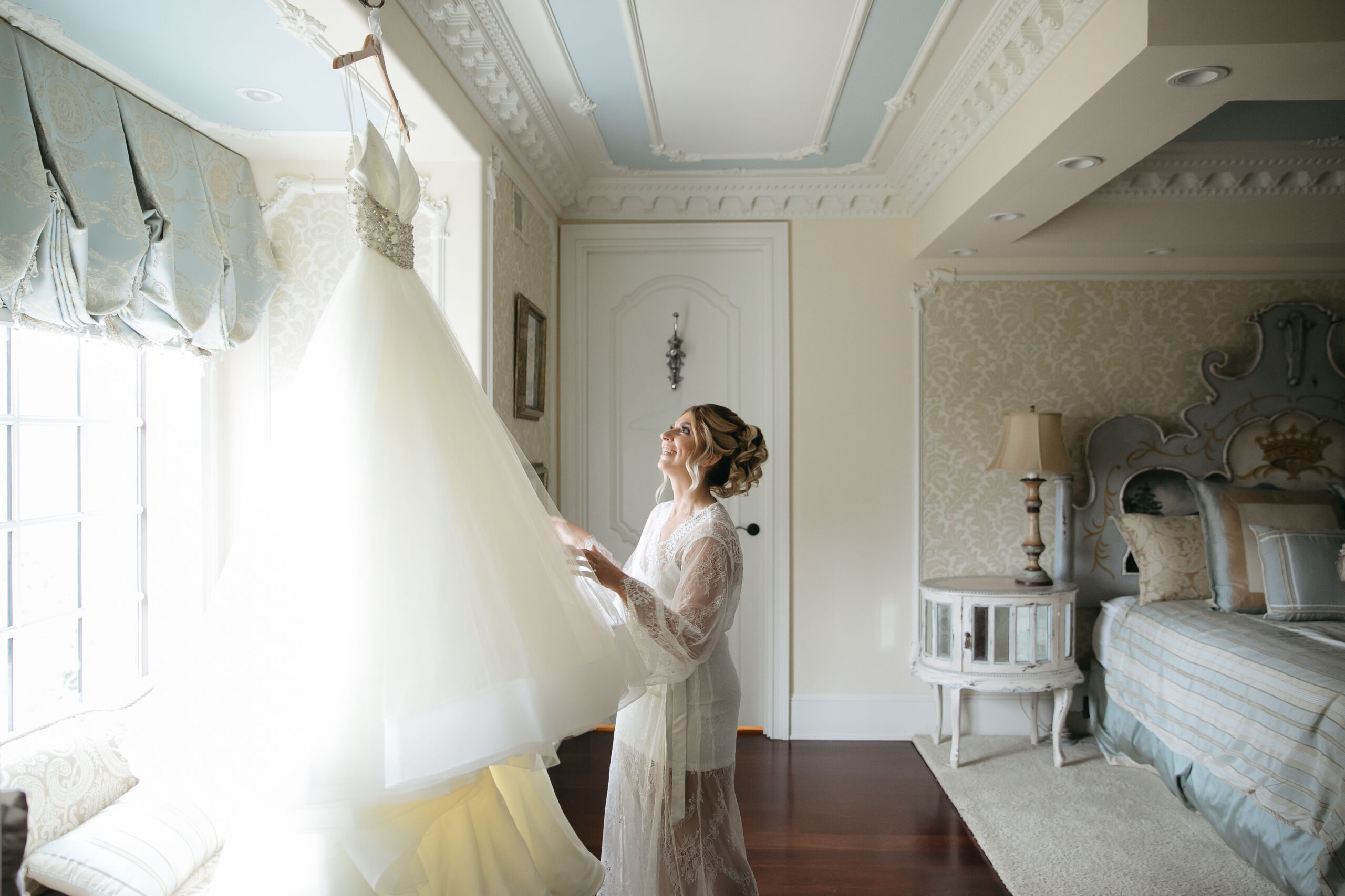 bride looking at her gown in window