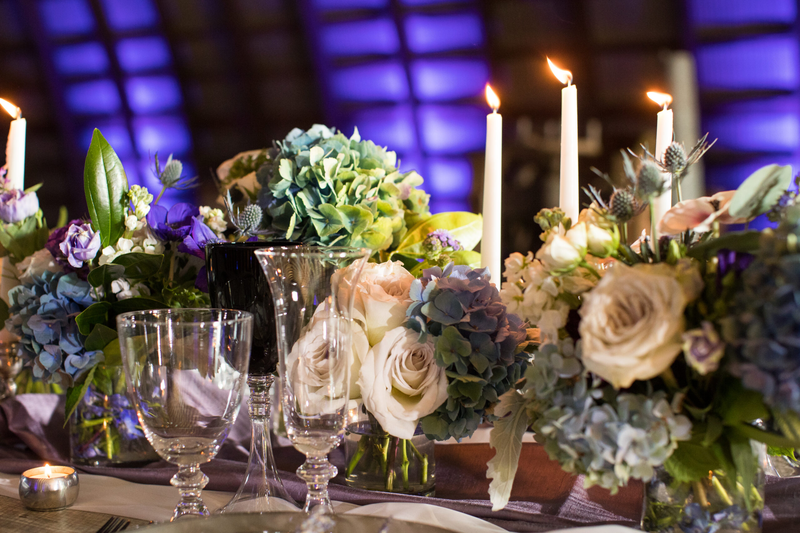 blue and purple lighting flowers long table