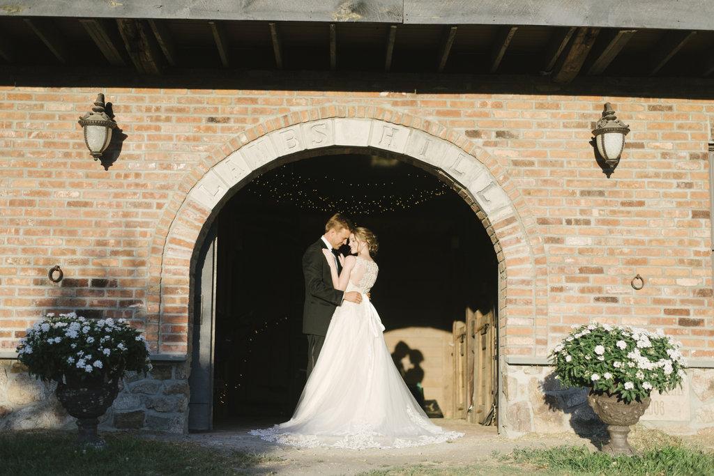 bride and groom embracing brick
