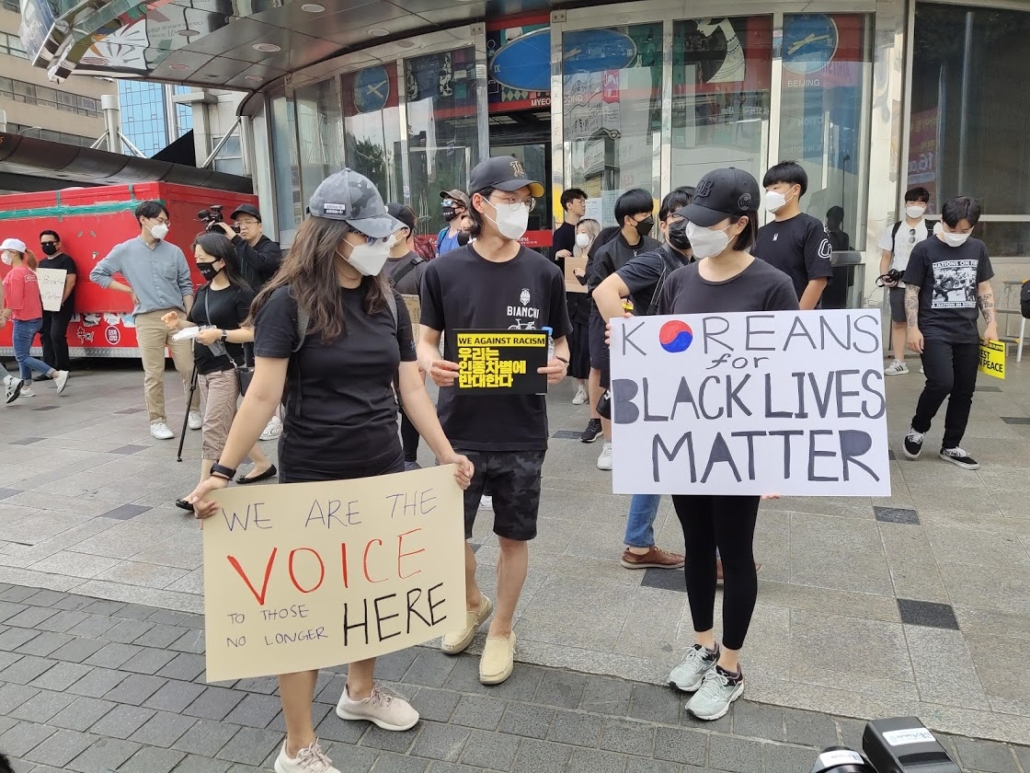 "Photos of protesters at Black Lives Matters protest in Seoul, South Korea. They hold signs bearing ""Koreans for Black Lives Matter,"" ""We Against Racism"" and ""We are the voice to those no longer here"" in English."