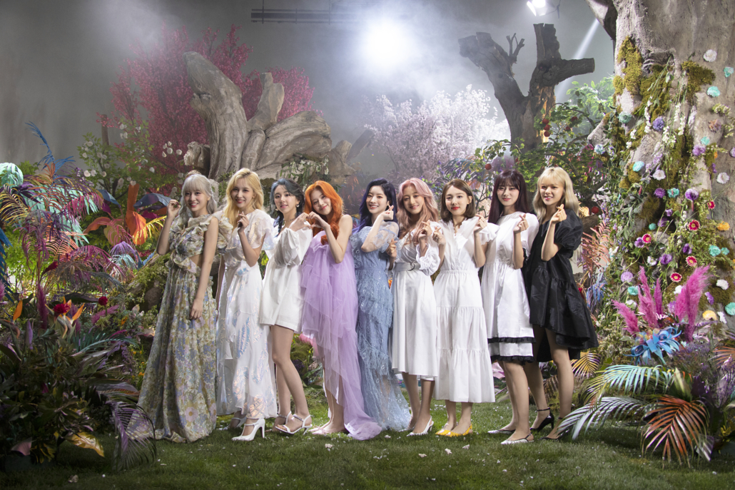 """TWICE posing with finger hearts on the forest set for the music video of """"More & More."""""""