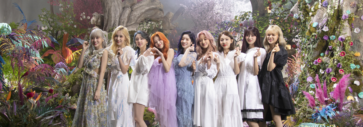 """TWICE's members posing with finger hearts on the set of the music video for """"More & More."""""""