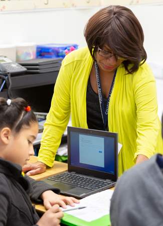 Photo: Teacher helping student with computer