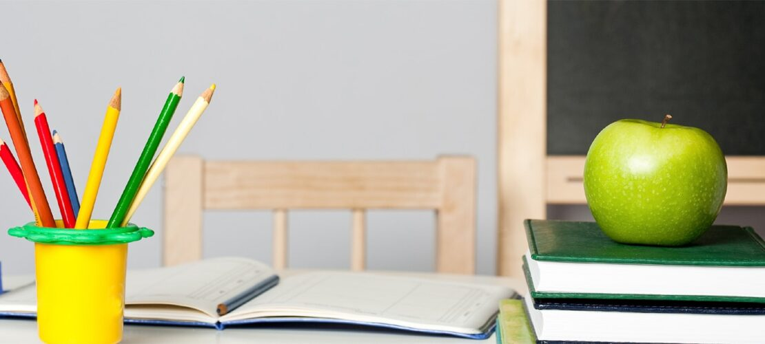 Photo: Pencils and an apple on teacher's desk