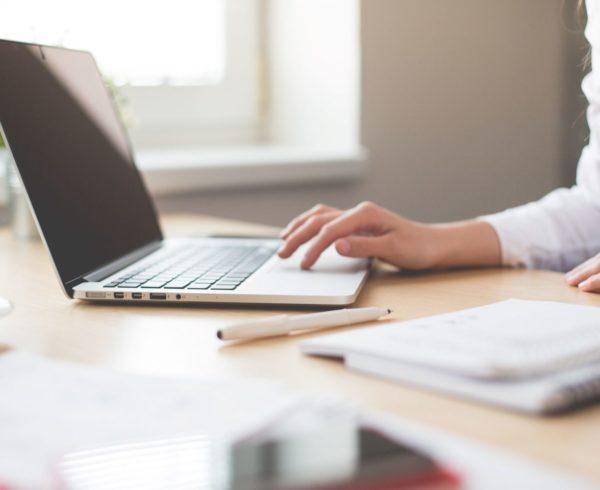 Female using laptop at office desk.