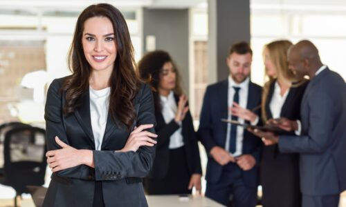 Businesswoman leader looking at camera in modern office with multi-ethnic businesspeople working at the background. Teamwork concept. Caucasian woman.