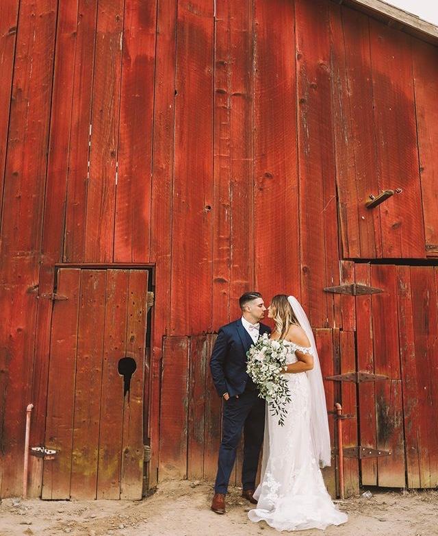 red barn behind bride and groom at california winery