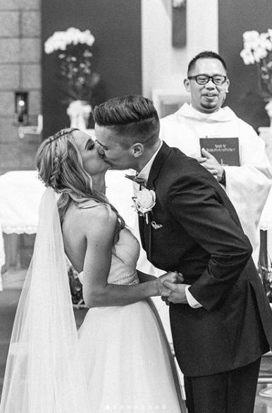 black and white kiss catholic church wedding ceremony