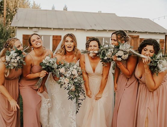bridesmaids in front of barn having fun