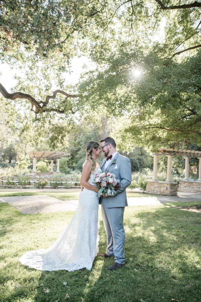 wedding couple outside green trees