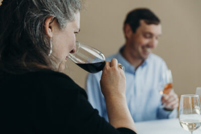 woman holding glass of red wine to her nose to smell aroma. Blurry image of a man is seen in background.