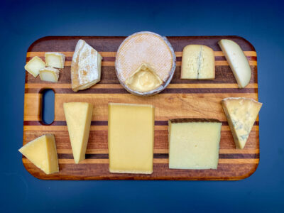 ten selections of cheese on a wood cutting board, seen from above.