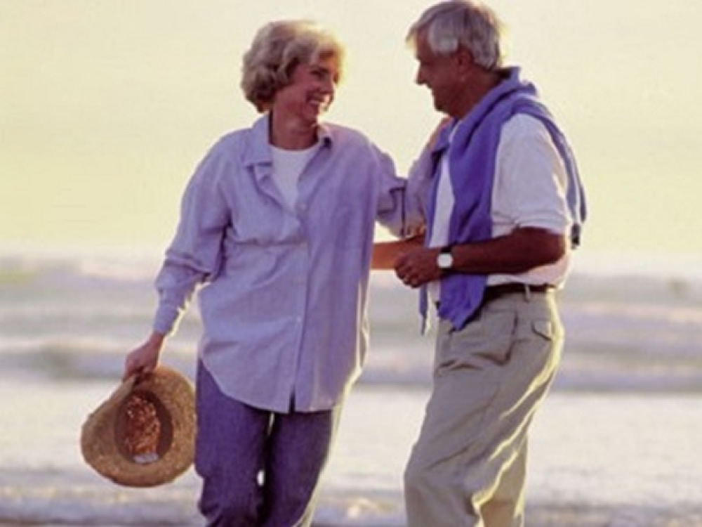 Happy retiree couple on beach are enjoying a successful retirement
