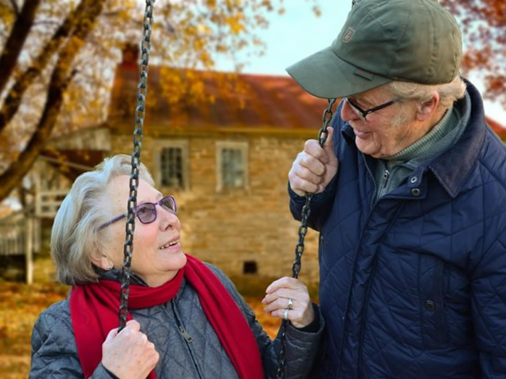Senior man talks to senior woman on swing about mortgage tips for retirement