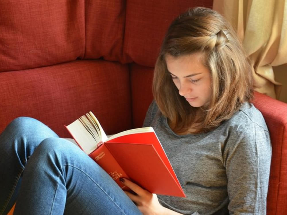 College student reading book on couch is subject to college funding decisions
