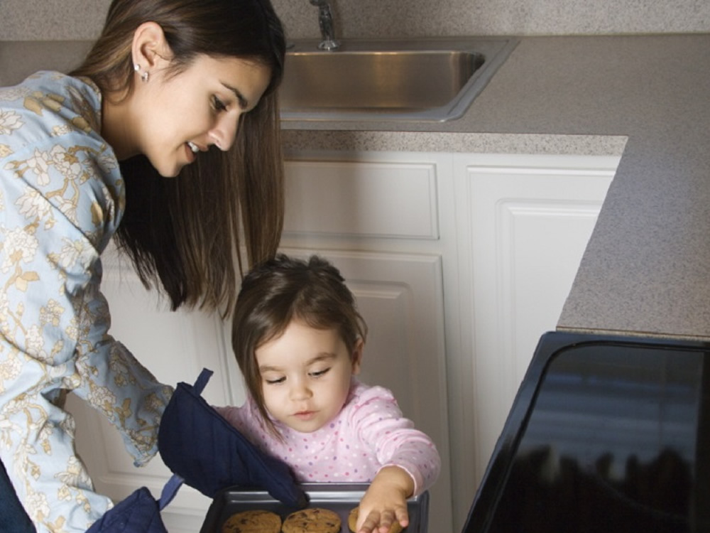 Domestic employee and toddler baking cookies together