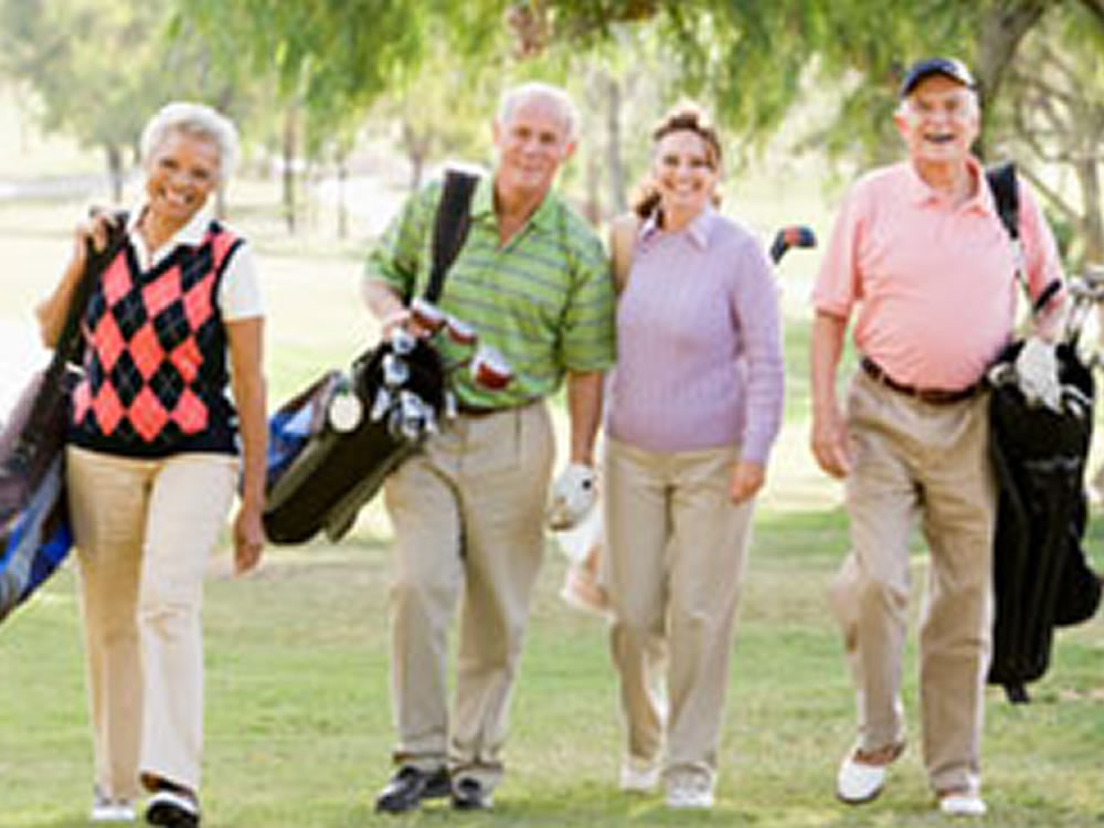 Two couples enjoy golfing after choosing a retirement community