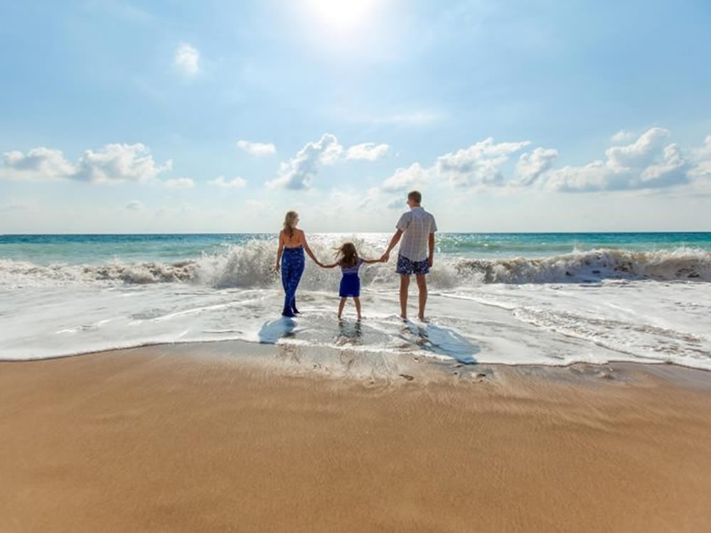 Couple and young daughter stand in the surf and save money on vacations