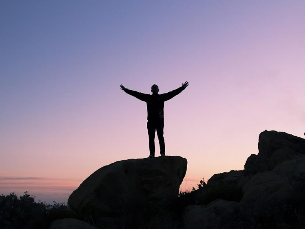 Man on mountaintop symbolizes financial success from maxing your 401(k)
