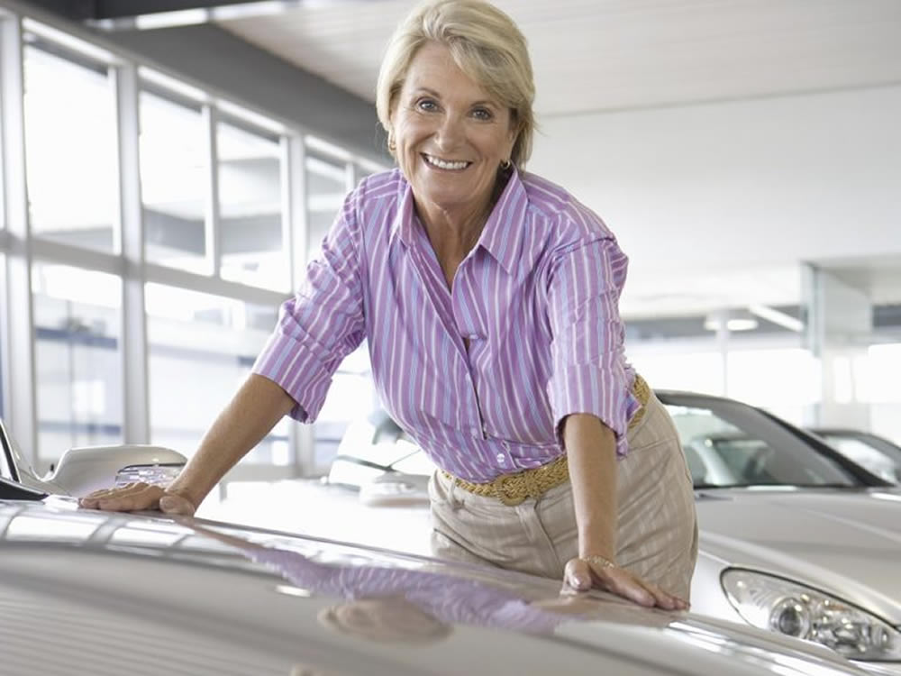 Woman retiree considers how to spend her pension option payout in new car salesroom