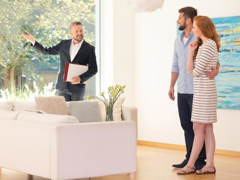 Realtor talks to young couple about the decision to rent or buy a home