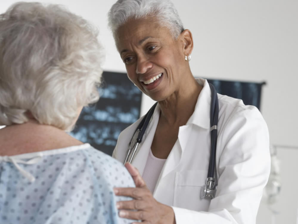 Female doctor talking to senior patient during Medicare check-up appointment