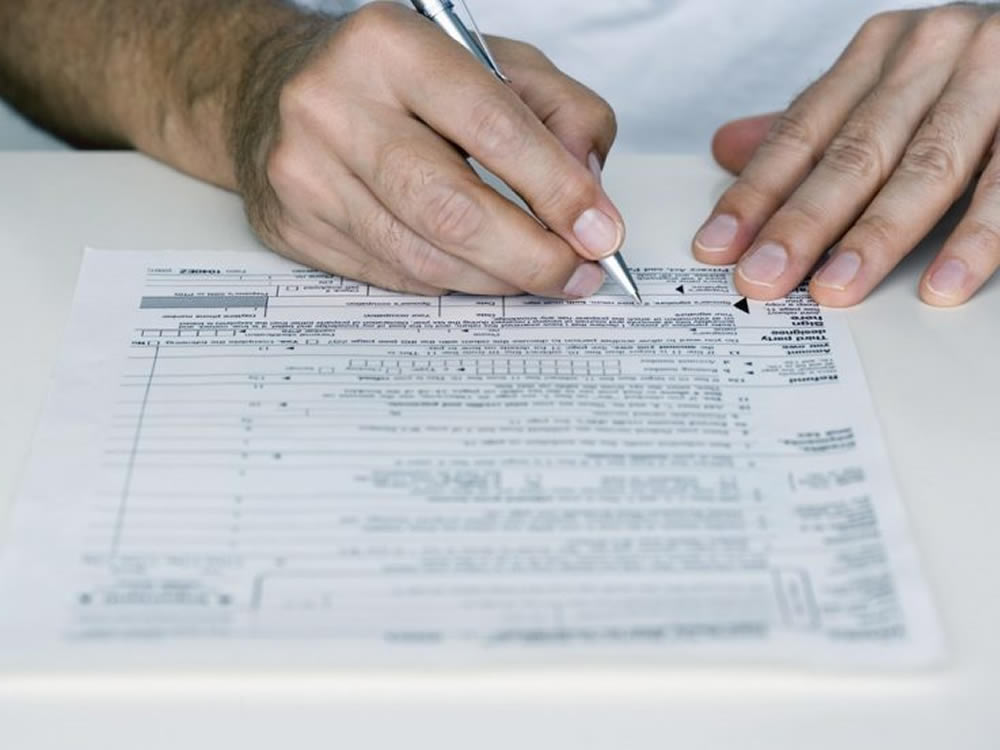 Man signing 1099 tax form considers what the tax reforms mean