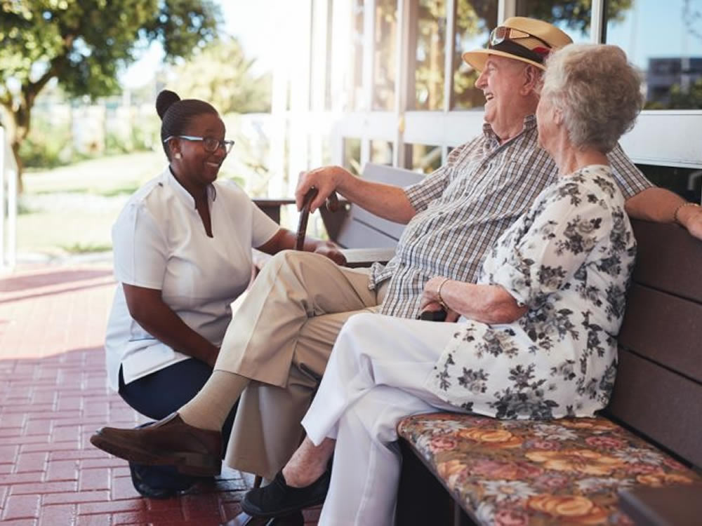 Nurse explains to elderly couple about long-term care insurance