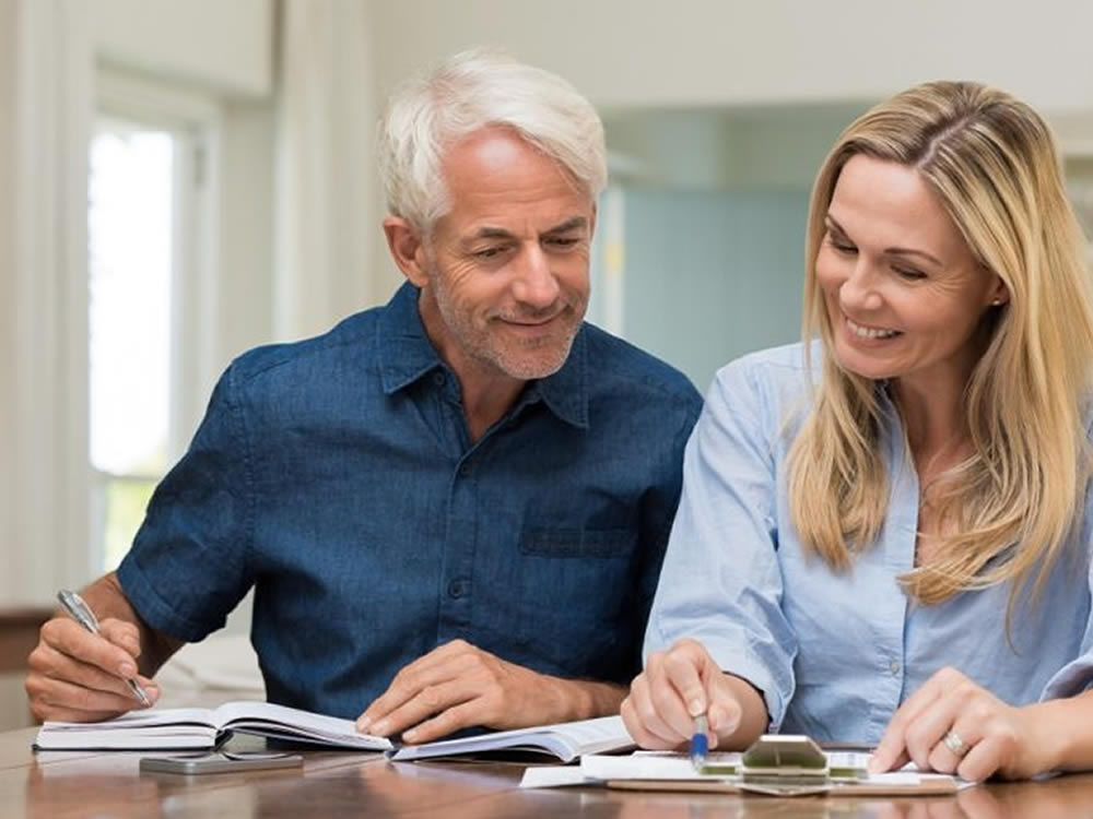 Happy couple check their finances with the SageVest Wealth Management quick review financial planning checklist