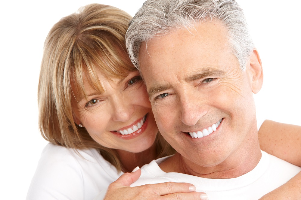 Older couple on white background, happy as they near retirement