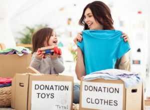 Mother and young daughter sorting donations to maximize charitable giving after tax reform