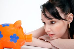 This teen with her colorful piggy bank is at the right age to teach your kids about investing