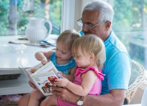 Grandfather reading to toddlers and considers grandkid's college costs