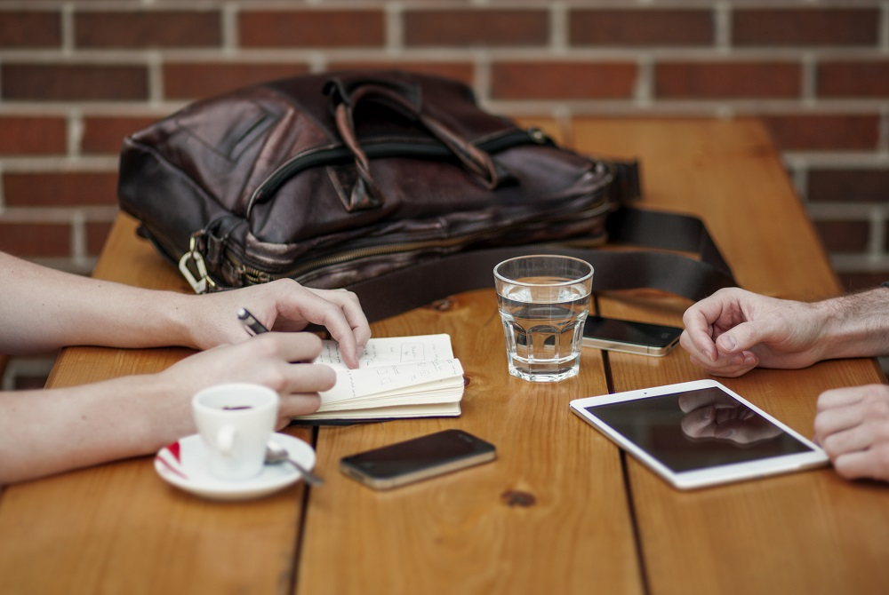 Man and woman talk at coffee table about the most common financial scams and how to avoid them