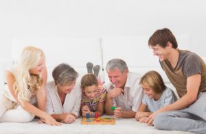 Family enjoyng playing fun financial board games for kids, tweens, and teens