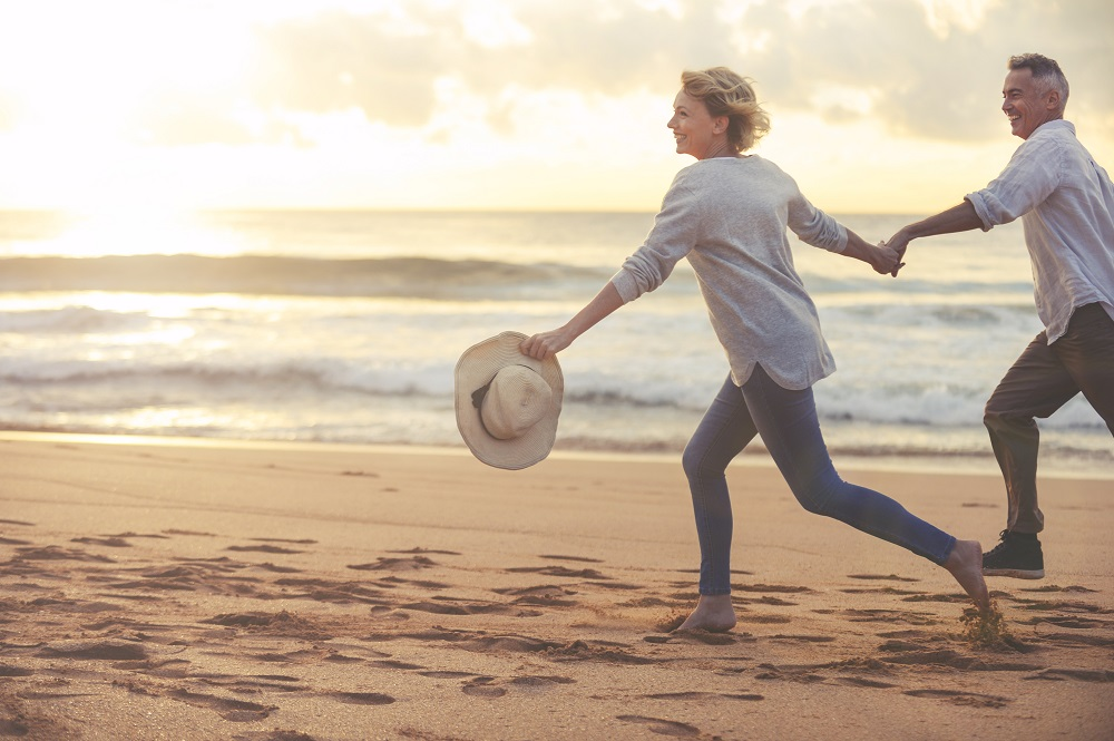 Happy couple running on beach have planned for how long you'll live in retirement