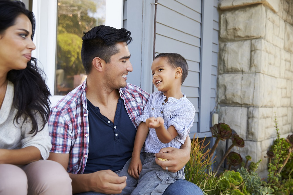 Mom, stepdad and child sitting on steps need help with estate planning for blended families