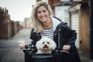 Woman cycling with dog in basket is ready to make claim for early Social Security retirement benefits