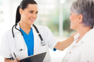 Female doctor explains Medicare enrollment to age 65 woman patient